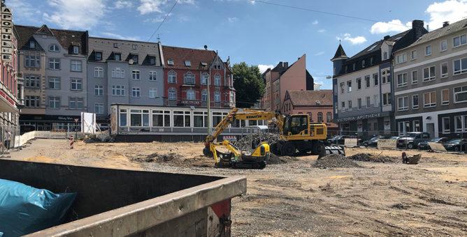Der Wilhelmsplatz als Baustelle von der Bismarckstraße aus gesehen. Mitten auf dem Platz steht ein großer Bagger.