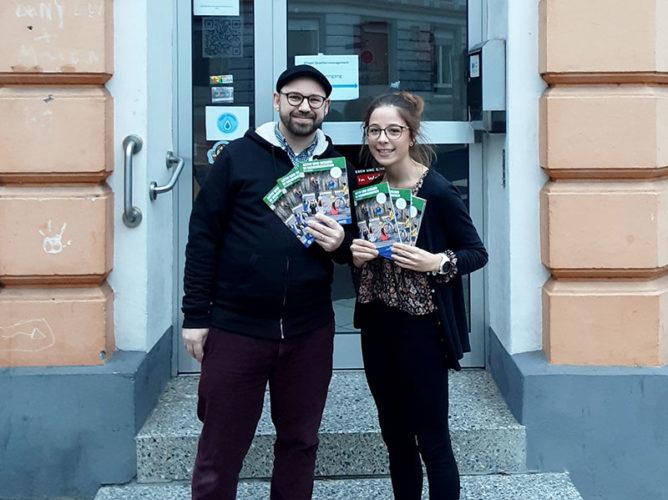 Jan Eckhoff und Malina König stehen vor dem Stadtteilladen und halten Magazine in den Hände.