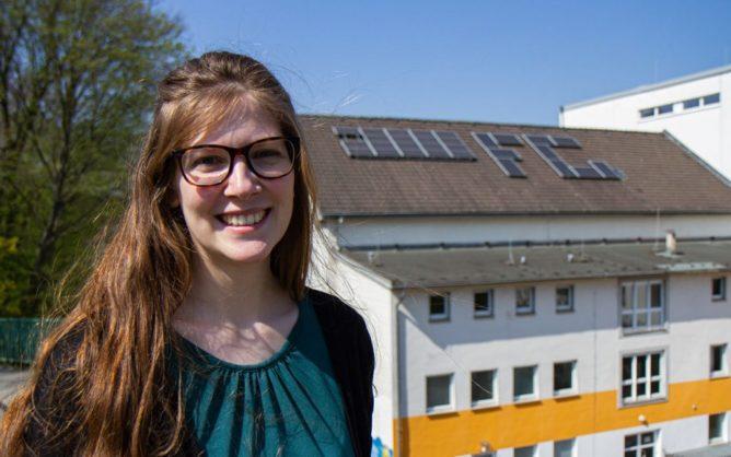 Porträtfoto Nicole Schulte, im Hintergrund das Dach des Fichte-Gymnasiums mit Solar-Anlage.