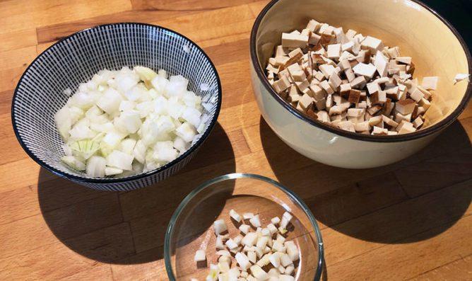 Schälchen mit kleingeschnittenen Zwiebeln, Räuchertofu und Knoblauch.