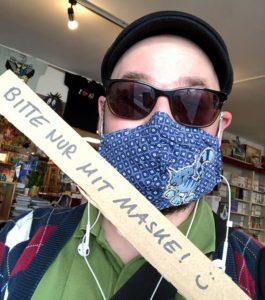 """Mensch mit Mund-Nasen-Schutz und Schild: """"Bitte nur mit Maske"""""""