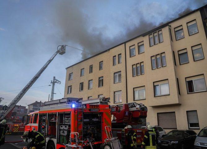 Feuerwehrfahrzeuge vor brennendem Haus