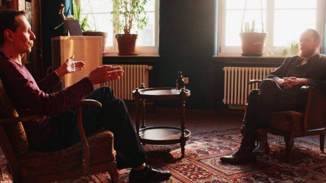 Zwei Männer sitzen sich in Sesseln gegenüber und reden.