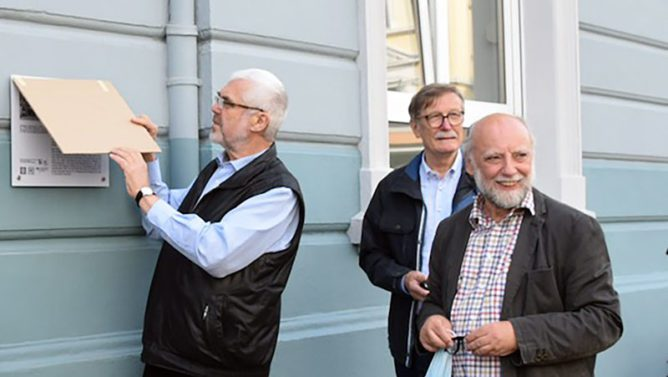 Drei Männer stehen vor einem Gebäude und enthüllen ein Schild.