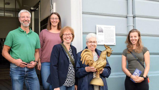 Fünf Personen stehen mit der Skulptur eines Hahns im Hauseingang.