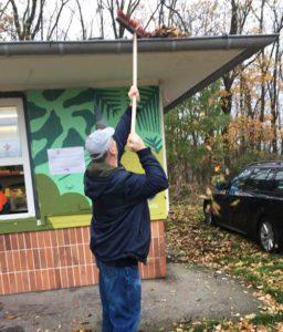 Mann säubert Dachrinne von Blättern