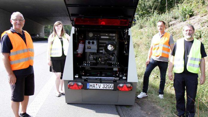 Vier Personen stehen an einer Straße mit dem neuen Blitz-Anhänger.